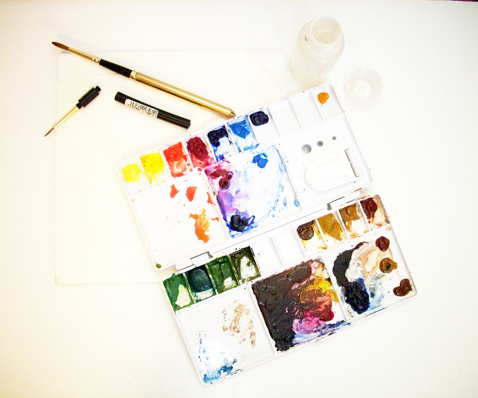 Watercolor field sketching palette, two paint brushes, and small water bottle