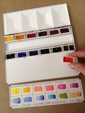 Watercolor paints in pans in a travel palette.